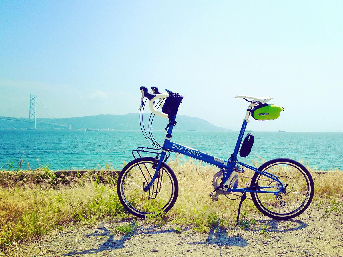 青い空と青い海。むこうには淡路島が見える。そんな景色の中に、青いフレームの折り畳みミニベロ「バイクフライデー・ニューワールドツーリスト」が置かれている真。