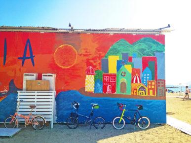 海水浴場の砂浜に建てられた「海の家」の裏側の壁にカラフルなアートがペイントされている。そのカラフルな壁を背景に、折り畳み小径車「ニューワールドツーリスト」と、ミニベロロード「コメットR」が停められている写真。地面は砂浜で、建物の向こうには青い海が見える。