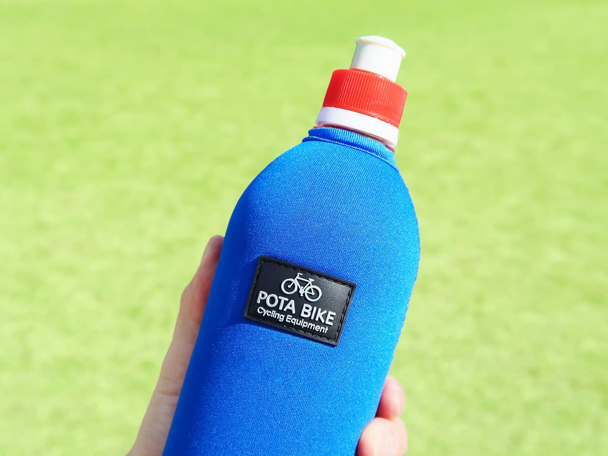 「POTABIKEペットボトルカバー」と「TNIの飲み口キャップ」が装着されたペットボトルを手に持っている写真