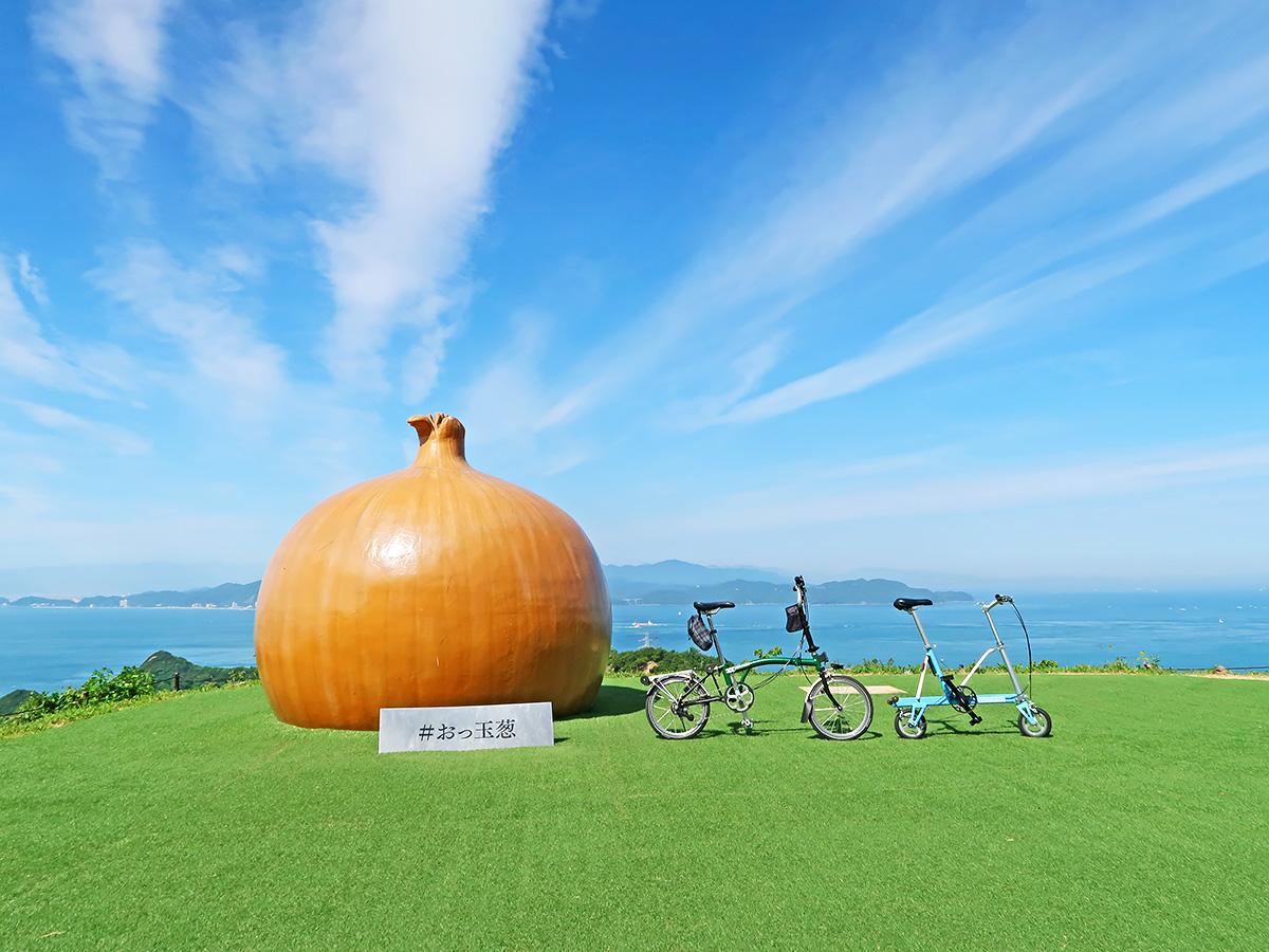 淡路島にある巨大な玉ねぎのオブジェ「おっ玉葱」と自転車を並べた写真