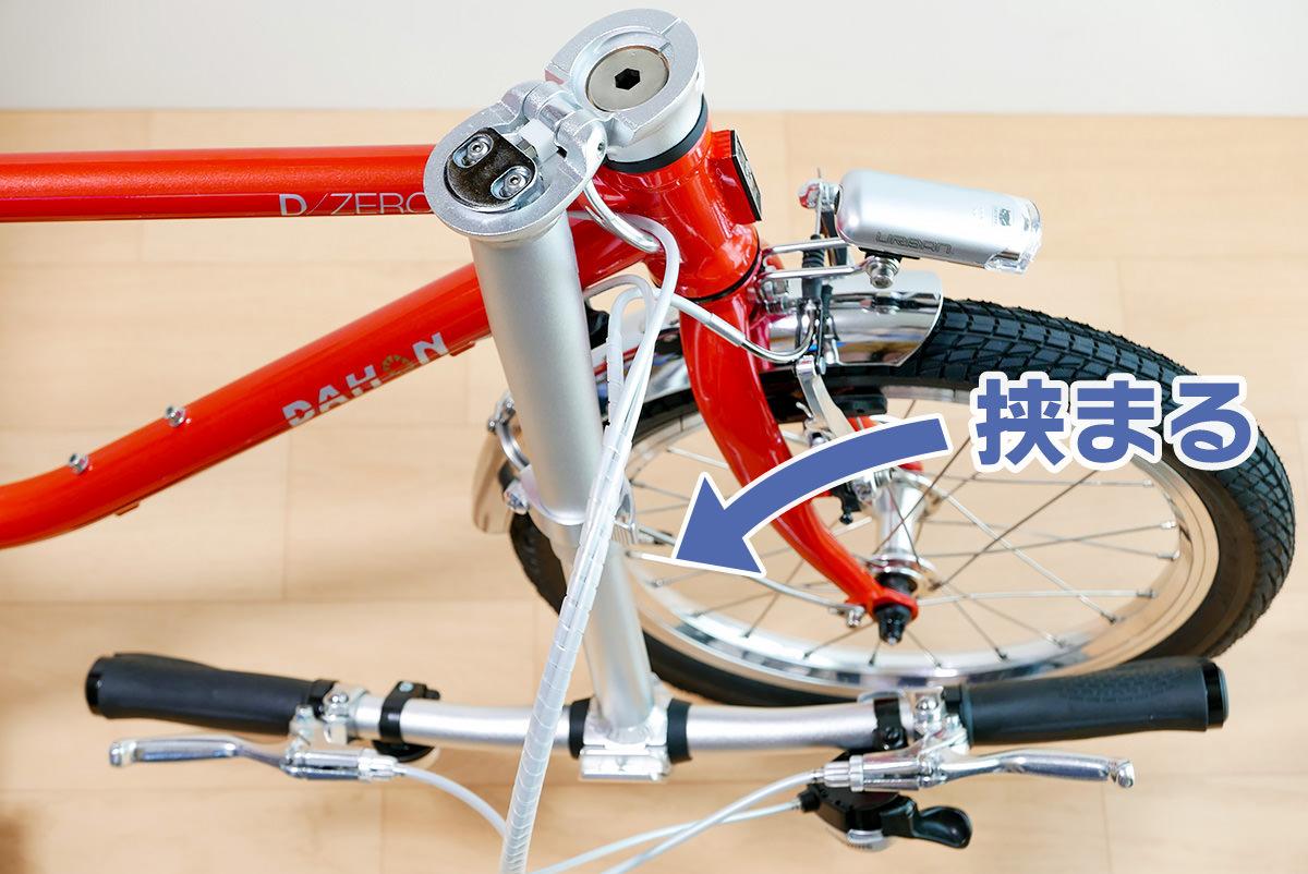 ダホンD-Zeroのハンドルを折り畳むと、ハンドルの手前側に装着したアイテムが挟まることを示した写真
