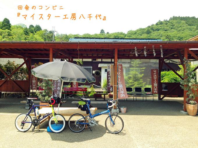 兵庫県多可郡多可町にある、田舎のコンビニ「マイスター工房八千代」の店舗前の写真。休憩用のパラソルの下に2台の自転車、「ニューワールドツーリスト」と「コメットR」が停められている。