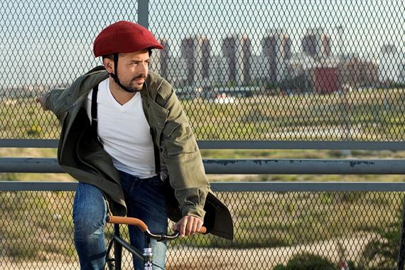 クロスカの赤いヘルメットを被った男性が自転車にまたがっている写真。