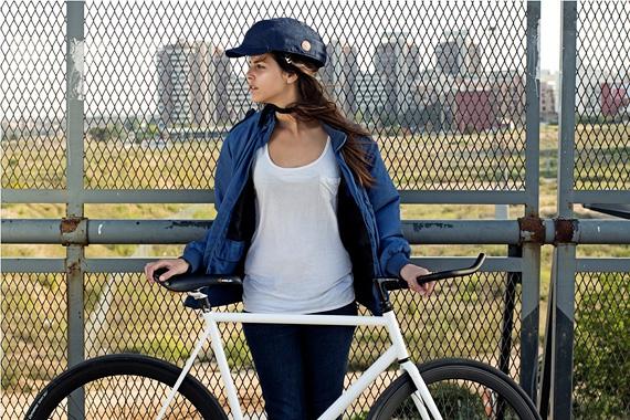 クロスカの青いヘルメットを被った女性が自転車の横に立っている写真。