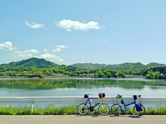 三田の青野ダムのダム湖「千丈寺湖」の風景。むこうには緑色の山々があり、湖面には山と青空が映っている。手前には2台の自転車、ニューワールドツーリストとコメットRが停められている。