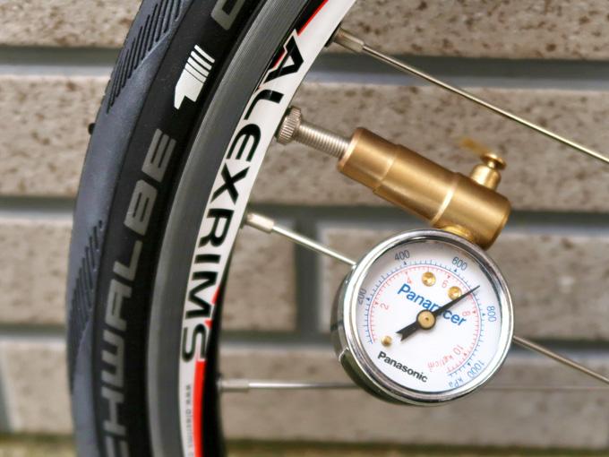 自転車のタイヤの空気圧を調節している写真。バルブに空気圧計が装着されている。
