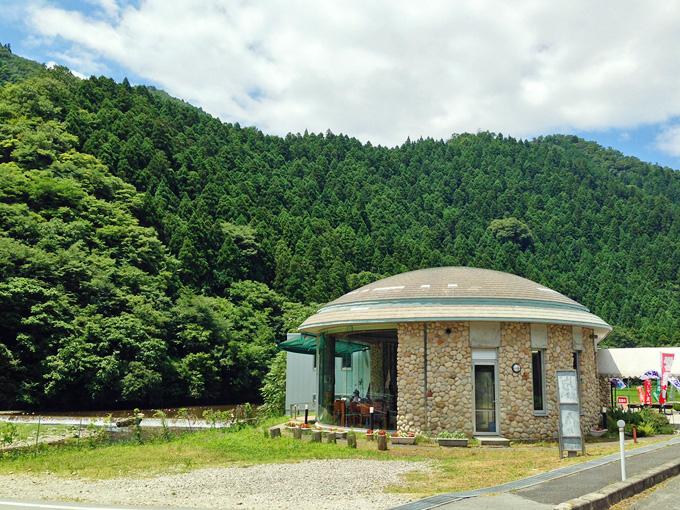 山すそを流れる川の横に建つ「南光ひまわり館」。丸い屋根の建物で、壁は一部が石で、一部は大きなガラス窓になっている。