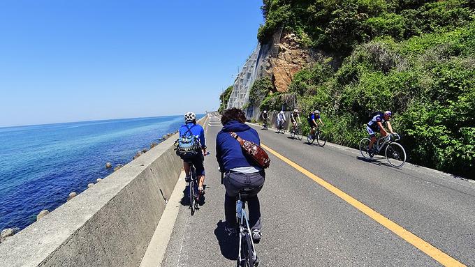 淡路島・五色浜付近の風景の写真。道路の右側は岩壁になっていて、左側には青い海が広がっている。