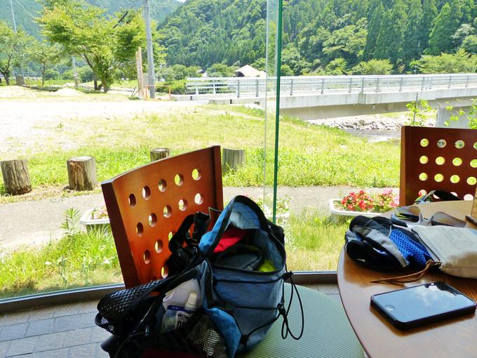「南光ひまわり館」の中から見る景色。大きなガラス窓の外には、草むらや川が見える。