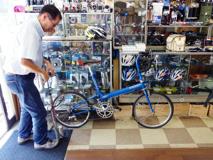 イトーサイクルの店内で、バイクフライデーのロードバイク「ポケットロケット」を写した写真。店主のおじさんがフロアポンプを使ってポケットロケットのタイヤに空気を入れている。