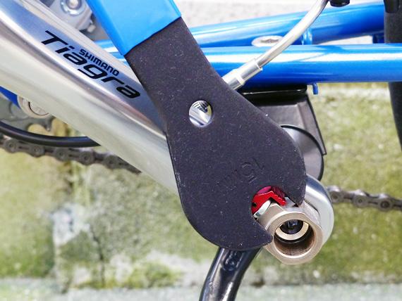 「Wellgo(ウェルゴ)」の着脱式ペダル「QRD」のアダプター部分が自転車のクランクに取り付けられている写真。一般的な15mmのクランクレンチが添えられているが、QRDのアダプターはそれより大きく、一般的なクランクレンチが使用できないことがわかる。