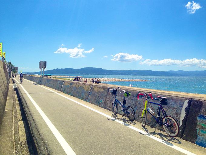 播磨サイクリングロードの「松江」付近の写真。海側の壁にはカラフルな絵が描かれていて、その前に2台の自転車、バイクフライデーの折り畳みミニベロ「ニューワールドツーリスト」とフジのミニベロロード「コメットR」が停められている。むこうには青い海と淡路島が見える。
