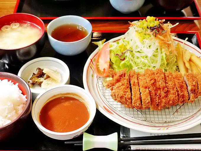 「ママン」の特上ロースカツ定食の写真。大きなトンカツ、サラダ、味噌汁、ごはんなどが並んでいる。