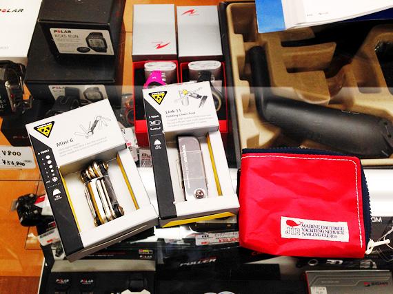 自転車用の携帯用工具が2種類と、赤いポーチが1つ、ガラス製の台の上に置かれた写真。