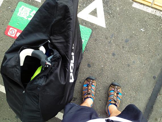 折りたたんで袋に収納された自転車「ニューワールドツーリスト」が駅のホームに置かれている写真。まもなく電車に乗るところ。