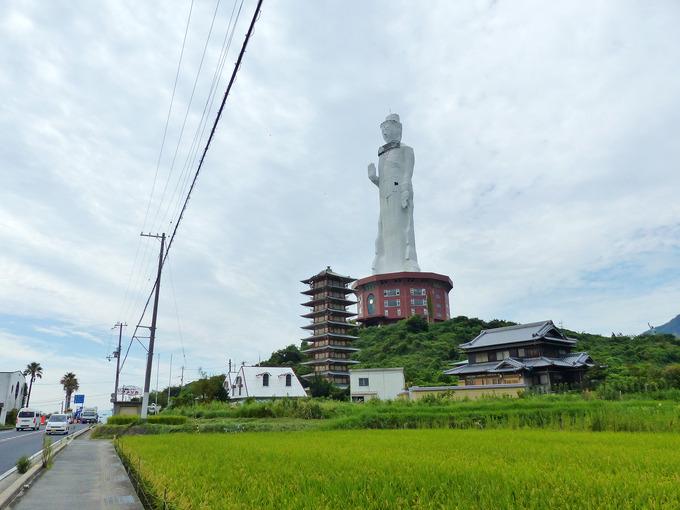 淡路島にある巨大な仏像「世界平和大観音像」付近の写真。巨大な仏像の下には、国道28号線の道路と、米が実った田んぼの風景がある。