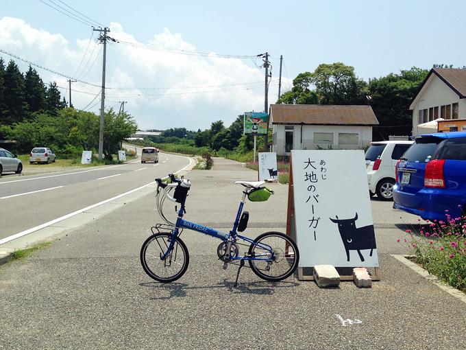 「あわじ大地のバーガー」と書かれた白い看板の横に、青い自転車「ニューワールドツーリスト」が停められている写真。