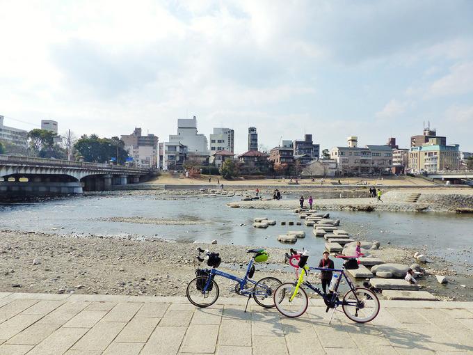 京都市左京区の「鴨川デルタ」付近の写真。加茂川と高野川が合流している様子が見える。鴨川デルタ周辺にはたくさんの人の姿がある。河川敷には2台の自転車、「ニューワールドツーリスト」と「コメットR」が停められている。