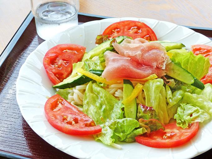 「サラダ風ひまわりうどん」。白い皿に冷たいうどん、その周りや上に赤いトマトや緑のレタス・キュウリ、黄色のパプリカ、生ハムが盛り付けられた料理。