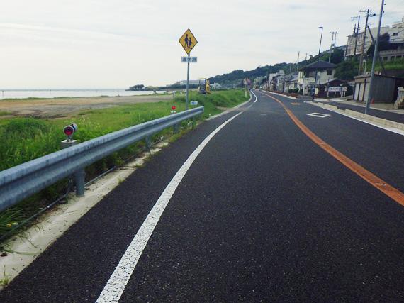 淡路島「岩屋」付近の国道28号線の道路の写真。左側には砂浜と海、右側には民家が見える。
