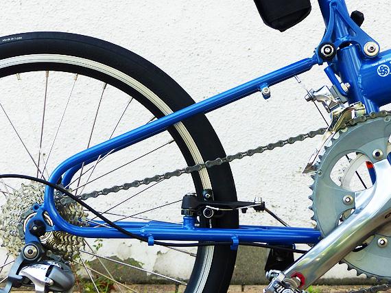 バイクフライデーの折り畳みミニベロ「ニューワールドツーリスト」の後部を真横から見た写真。細い青いパイプで作られた三角形のような形をした部分にギアやブレーキやタイヤなど色々な部品が装着されている。