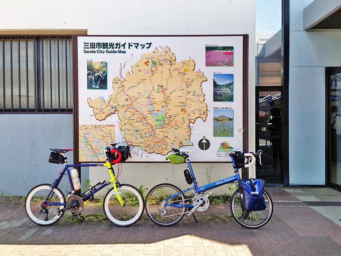JR新三田駅の前にある「三田市観光ガイドマップ」の写真。手前には2台の自転車、ニューワールドツーリストとコメットRが停められている。