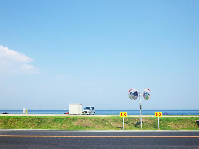 草が生えた緑色の斜面のむこうに、砂浜と青い海が見える。