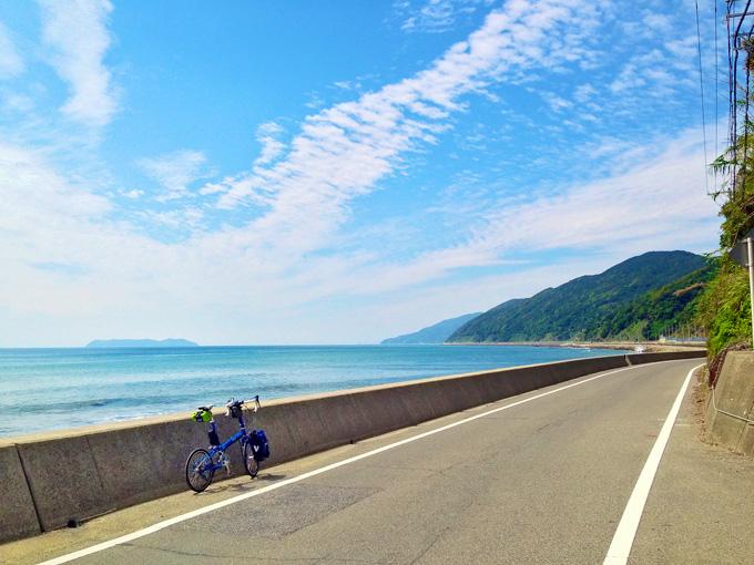 淡路島の南端付近の海岸線の風景。海岸線の道路「南淡路水仙ライン」から見る青い海、青い空、秋の雲の風景で、道路にはバイクフライデーの折り畳みミニベロ「ニューワールドツーリスト」が停められていて、海の向こうには小さな離島「沼島」が見える。