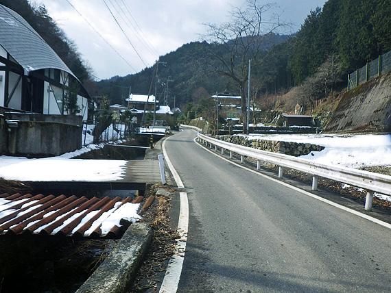 滋賀県大津市内の「途中越」付近の旧道の写真。道幅の狭い坂道が続いていて、道路脇には雪が積もっている。