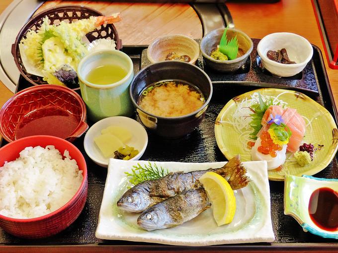 「グリーンエコー笠形」内にあるレストランのお食事「笠形御前」の写真。川魚「アマゴ」の塩焼きと、その他お刺身・天ぷらなど色々なお料理が並んでいる。