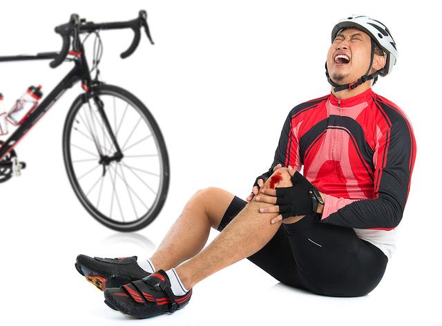 ロードバイクで転倒・落車して膝を怪我して痛がっている男性のイメージ画像。