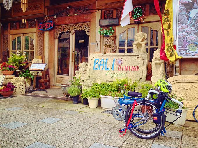 インドネシア料理店「バリラグーン」の店舗外観。木製の格子窓と複雑な装飾、人間の形の石造、南国をイメージさせる観葉植物や赤い花がある、独特の雰囲気のエクステリア。大きな石版にアルファベットで「バリラグーン」と書かれている。