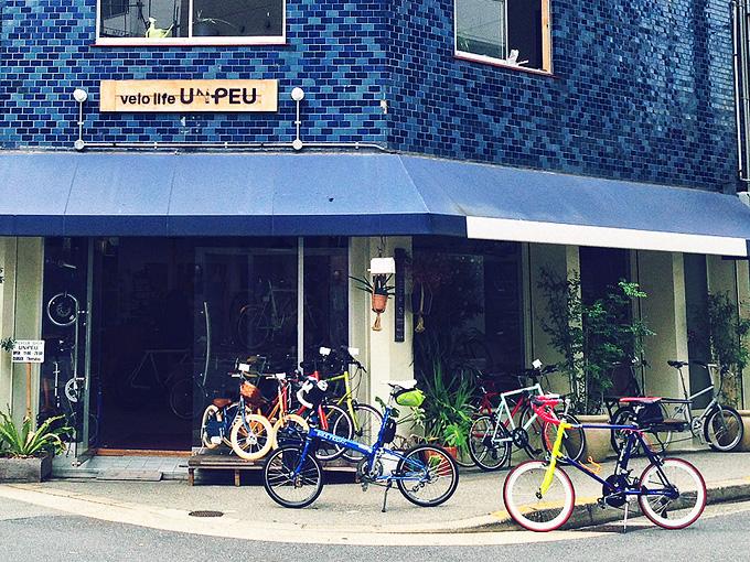 大阪の南堀江にある自転車屋さん「ヴェロライフ・アンプ」の店舗の外観の写真。青いタイル貼りの壁の建物で、入り口には青いテントが付けられている。商品の自転車が何台か並べられていて、その前に筆者の自転車「バイクフライデーのニューワールドツーリスト」と、友人の自転車「コメットR」が停められている。