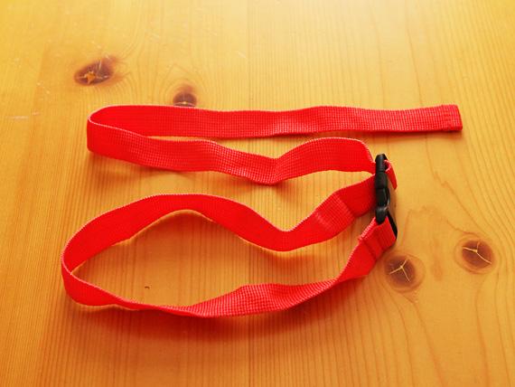 ナイロン製の赤いベルトの写真。途中に黒いバックルが付いている。