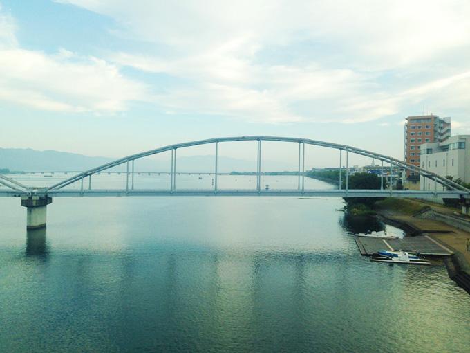 滋賀県に向かう電車の車窓から見た朝の風景。電車は川に架かる橋の上を通過している所で、下には川、むこうには橋が見える。