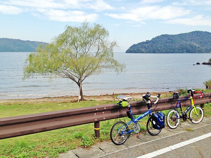 滋賀県近江八幡市の琵琶湖湖岸の「宮ヶ浜」の写真。ガードレールのむこうに柳の木が立っている。そのむこうには琵琶湖が広がっている。道路脇にはバイクフライデーの折り畳みミニベロ「ニューワールドツーリスト」と友人のミニベロロード「コメットR」が停められている