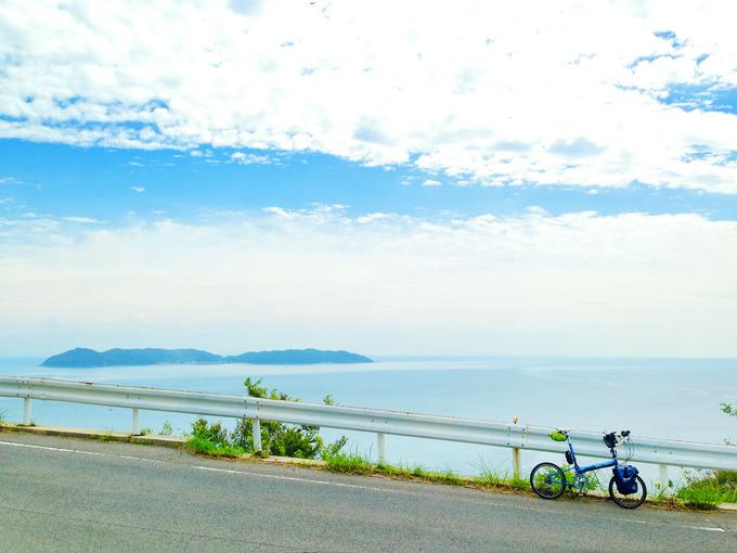 南あわじ市の山道の風景。道路の向こうには青い海が広がり、海の向こうには離島「沼島」が見える。道路脇には白いガードレールがあり、ガードレールの前にバイクフライデーの折り畳みミニベロ「ニューワールドツーリスト」が停められている。この場所は急勾配な下り坂で、ニューワールドツーリストは斜め下を向いている。
