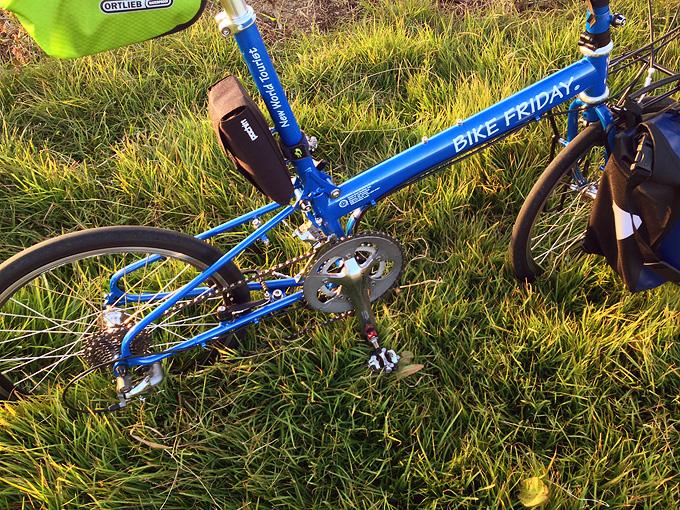 バイクフライデーの折り畳みミニベロ「ニューワールドツーリスト」が緑色の草むらに停められている写真。
