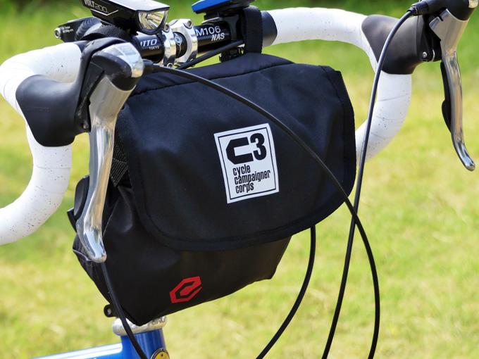 フロントバッグ「シースリーショルダーS」が自転車のハンドルに装着されている写真。バッグの蓋として前面にフラップが付いているのがわかる。