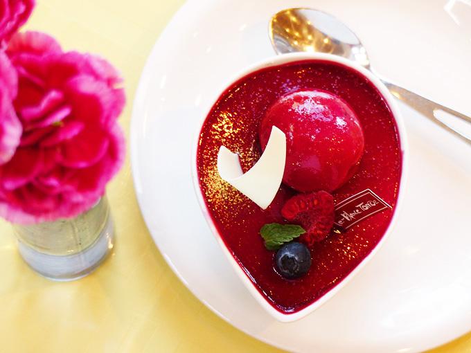 「レア&マロン」というケーキの写真。白い深い器に、真っ赤なアドベリーソースを使ったケーキが入っている。