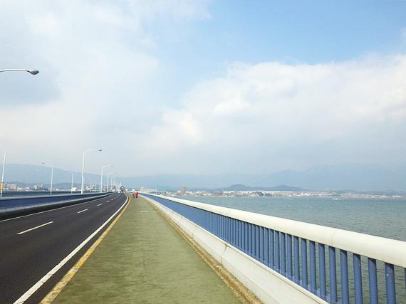 琵琶湖大橋の歩道から見た風景。左側には車道があり、右側には琵琶湖の水面が広がっている。
