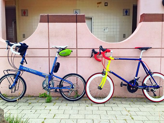 ピンク色のペンキで塗られたコンクリート製の壁に2台の自転車、バイクフライデー「ニューワールドツーリスト」とフジ「コメットR」が寄りかかるように停められている写真。