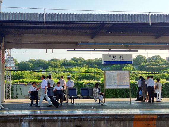 朝の「JR明石駅」のホーム。通勤や出掛ける人がまばらにいて電車を待っている。ホームのむこうに明石公園の緑色の木々や明石城が見える。