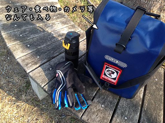 木製のベンチに置かれたオルトリーブのパニアバッグ「フロントローラークラシック」と「魔法瓶型のボトル」と「自転車用のグローブ」の写真。