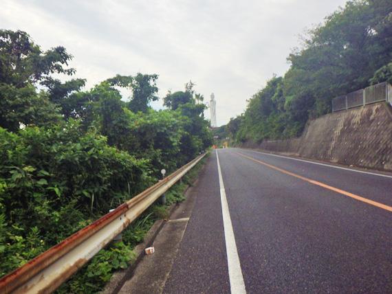 淡路島の北東部の町「仮屋」付近の国道28号線の道路上から見た風景。左右に木々が生い茂り、道路の先には遠くに白い大きな観音像が見える。