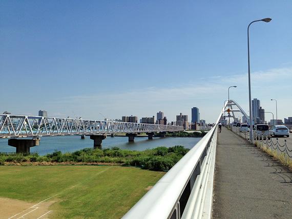 大阪市内、淀川にかかる橋「長柄橋」を西端付近から見た写真。白いアーチ状の橋がかかっている。眼下には芝生広場や淀川の流れが見える。
