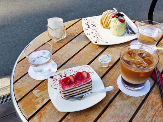 「北浜スイーツ・フォーチェ」の屋外席のテーブルにケーキと飲み物が並べられた写真。