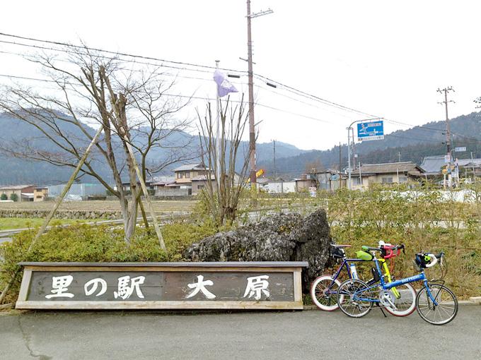 「里の駅・大原」と書かれた看板の横に2台の自転車、「ニューワールドツーリスト」と「コメットR」が停められている写真。