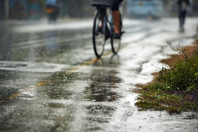 雨で濡れた道路を自転車に乗った人が走っている様子。