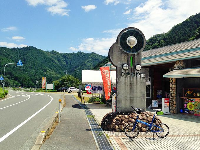 「南光ひまわり館」の道路側の写真。「ひまわり館」と書かれたコンクリート製のオブジェがあり、その下にバイクフライデーの折り畳みミニベロ「ニューワールドツーリスト」が停められている。